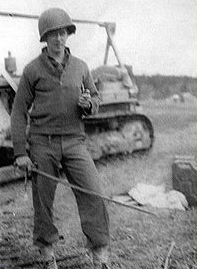 Nineteen year-old Arthur W. Jasper standing in front of a bulldozer and holding a German sword. This was in Germany, probably around April 1945.