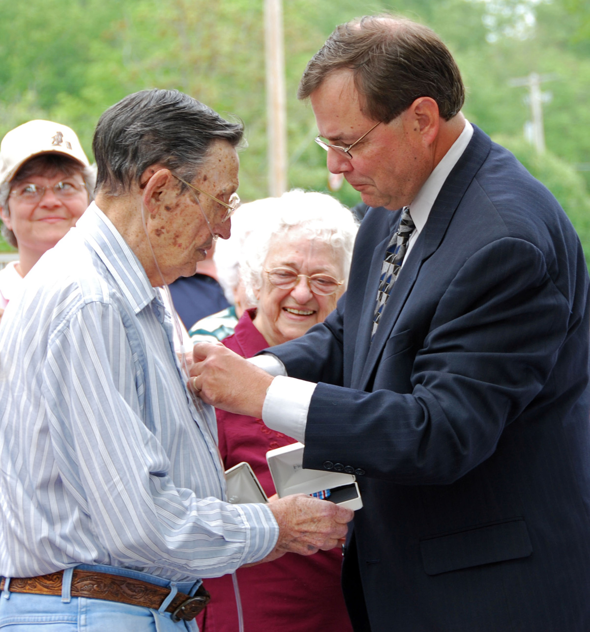 "James Dee pins the Honorable Service Lapel Pin, ""Ruptured Duck"", on Gene Broughton as his wife Mattie Jo looks on."