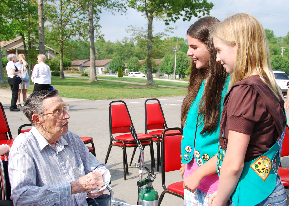 Gene Broughton talks to Girl Scouts Amanda Dee and Kaleigh Lain after the ceremony.